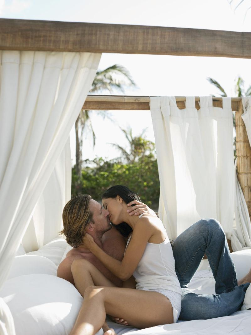 床上亲吻的情侣夫妇