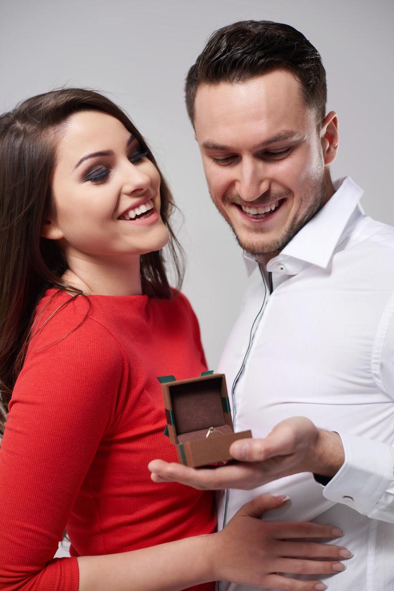 一对恩爱的情侣手里拿着的订婚戒指