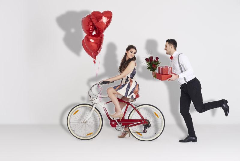 骑着自行车的美女身后有个拿着花和礼物的男人