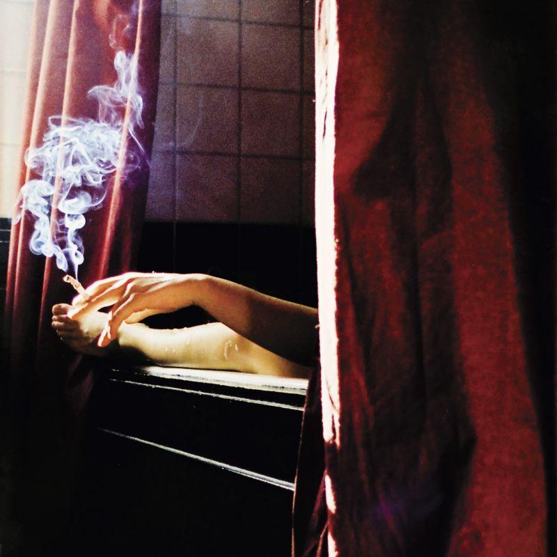 正在卧室吸烟的成年男子