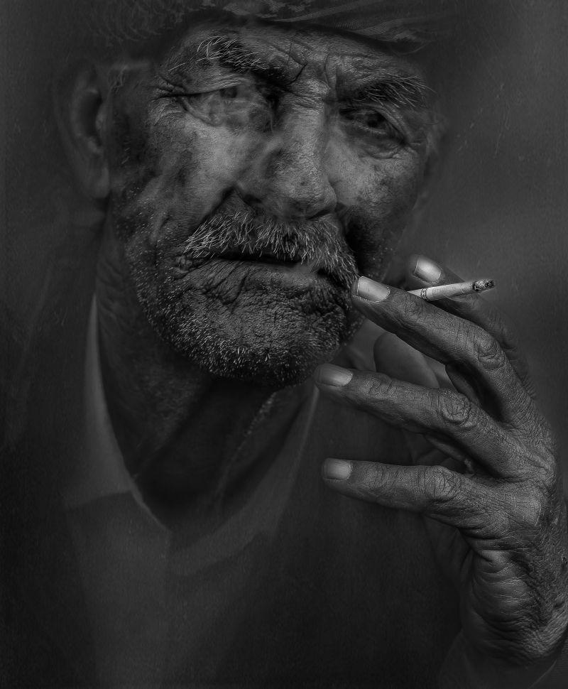 在黑暗的背景下正在吸烟的吸烟者