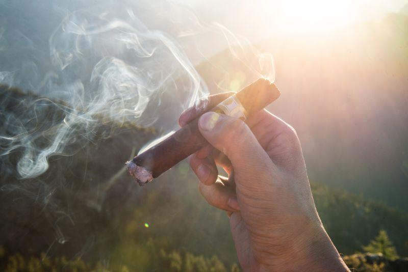 单手拿着雪茄的烟强烈的冒着