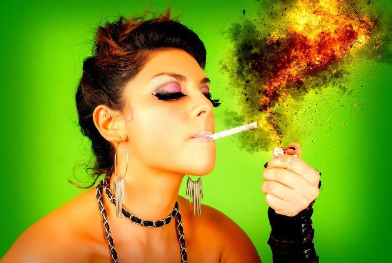 在绿色背景下正在用打火机给香烟点火的美女