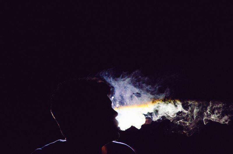 在黑暗中吸烟的成年男子