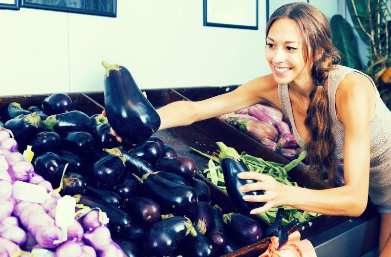 在市场上选择新鲜茄子的美女
