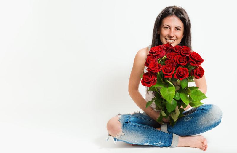 坐在地下拿着花的美女