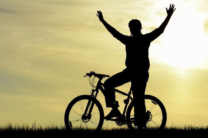 日落下骑自行车的人剪影
