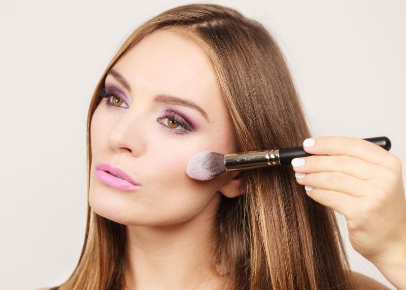 女人把胭脂抹在脸上