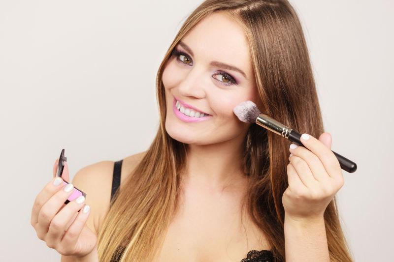 漂亮的女孩拿着化妆刷微笑着化妆