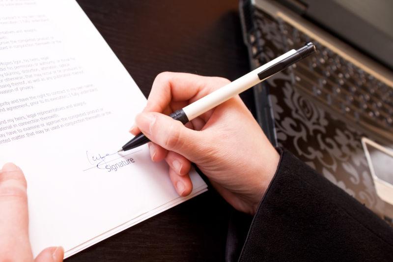 特写镜头的商人手拿着钢笔和签署的文件
