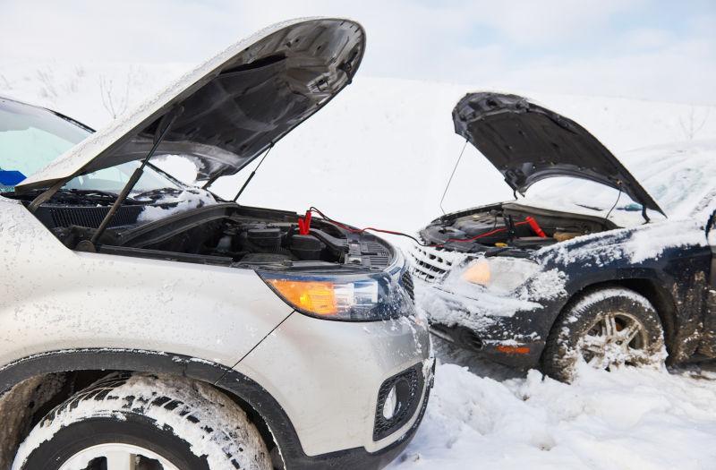 雪地里从一辆车发动机给另一辆汽车充电