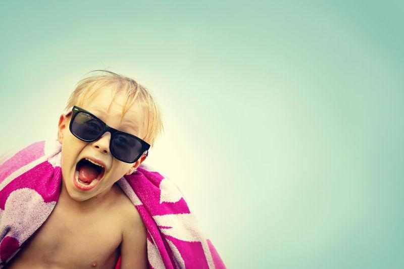 一个超级快乐的男孩在海滩上对着相机微笑
