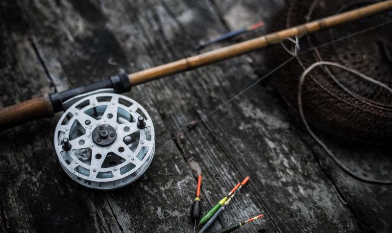 黑色木背景上的老式鱼竿和鱼漂