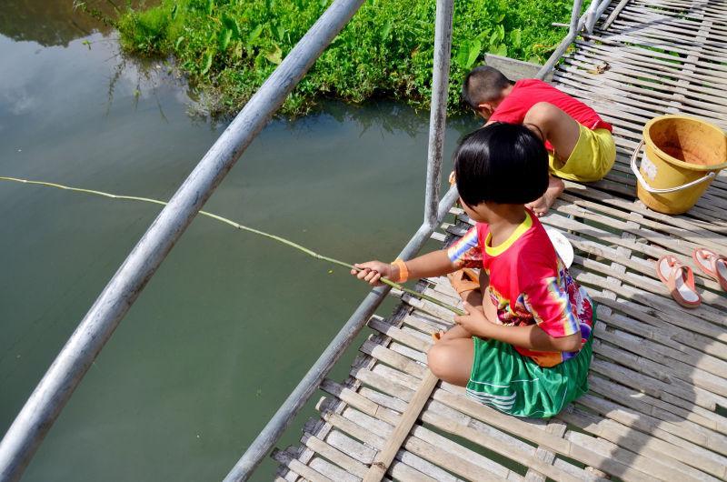 竹节桥上钓鱼的孩子