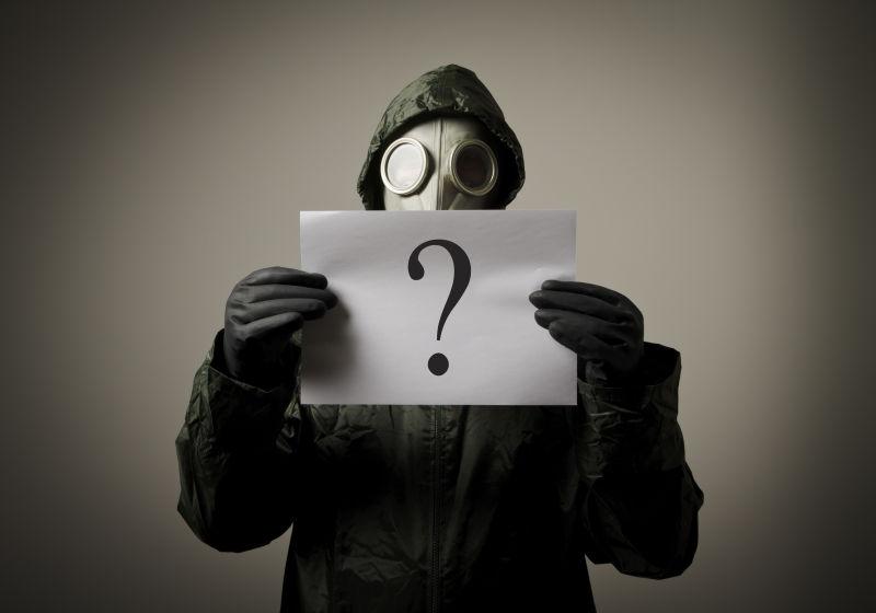穿防毒面具的人手里拿着疑问的纸张