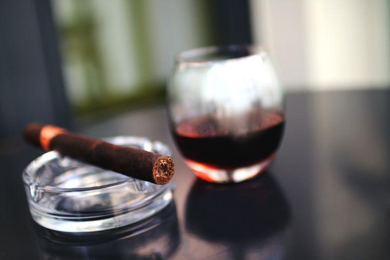 黑色桌面上的雪茄和红酒杯