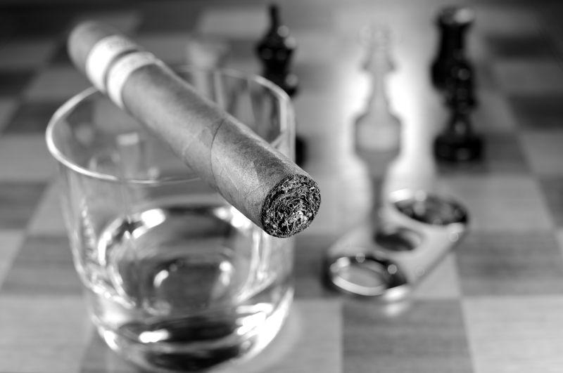 灰色背景中的玻璃杯和雪茄
