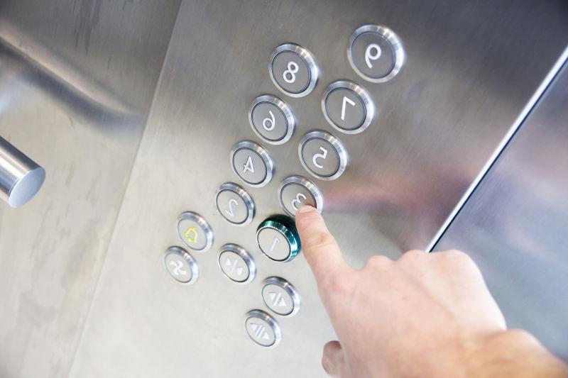一只手正在安电梯里的按钮