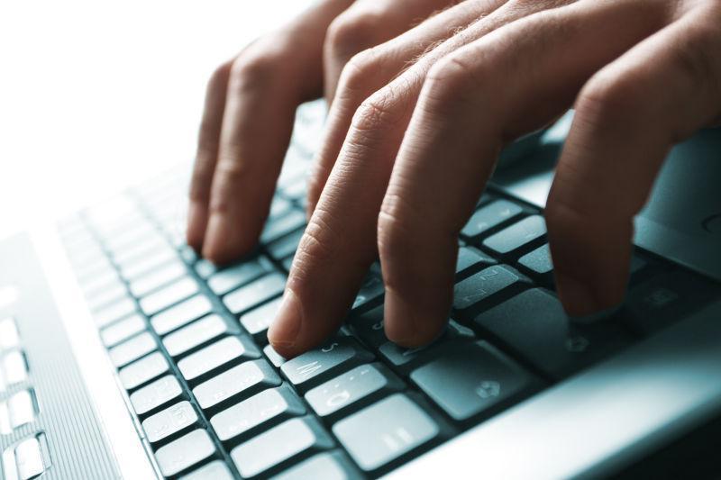 有明亮光线背景下在笔记本电脑键盘上打字的男性手