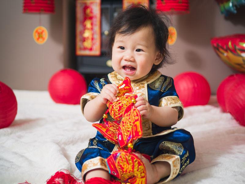 婴儿开怀大笑的在玩着春节装饰品