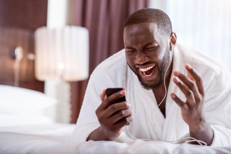 趴在床上看着手机的黑人