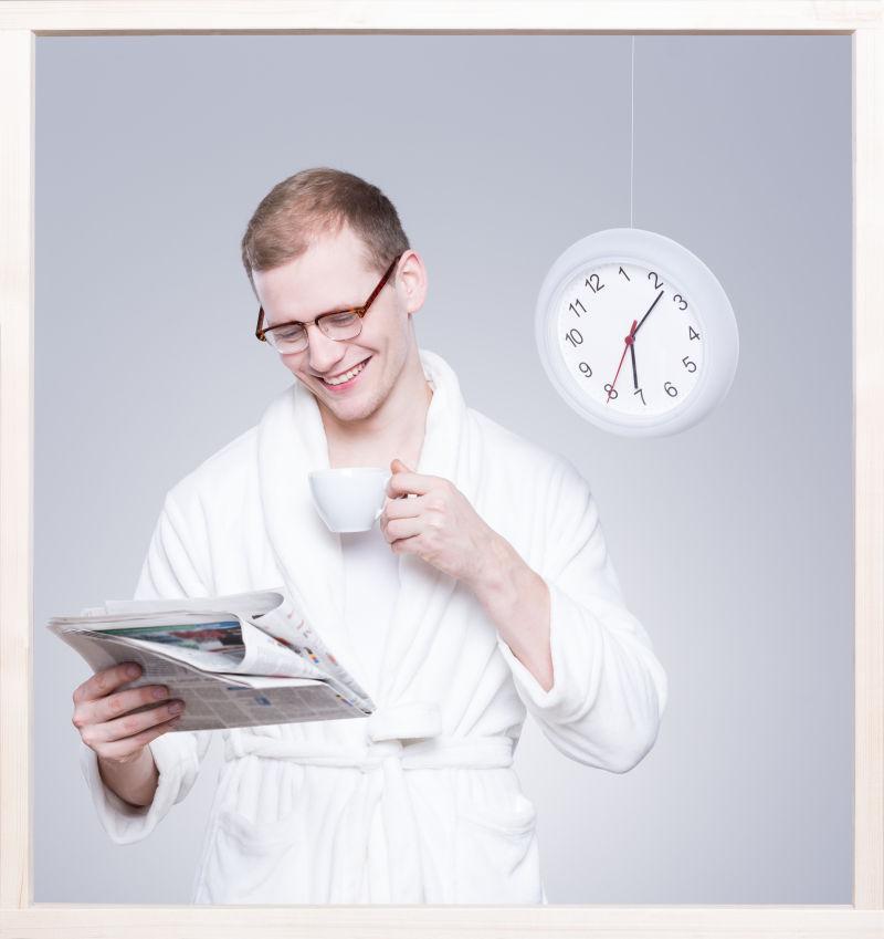 灰色背景上一个穿着浴袍看报纸的男人