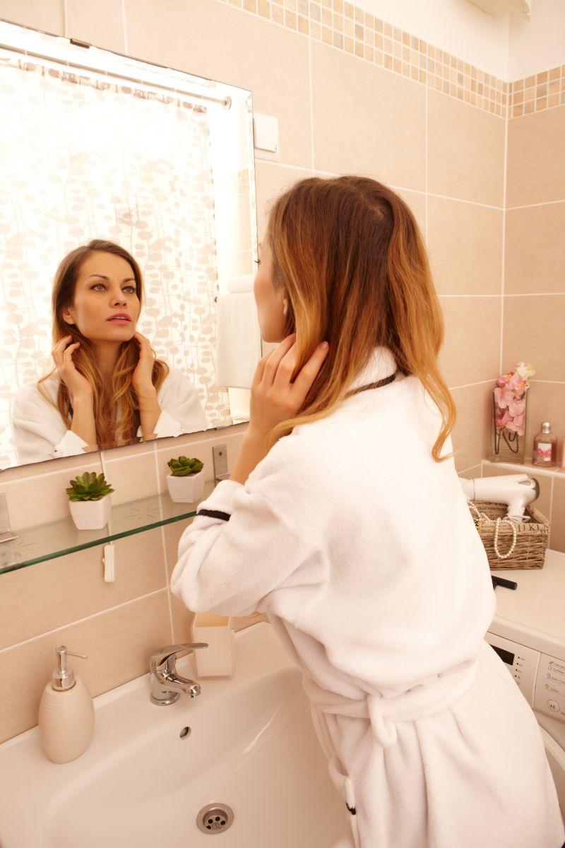 在浴室里穿着浴袍照镜子的女人