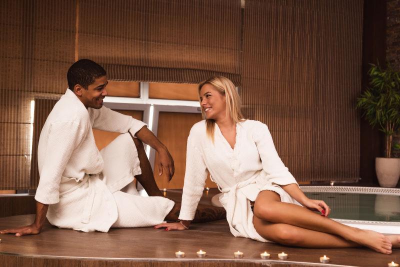 穿着浴袍坐在地板上聊天的情侣