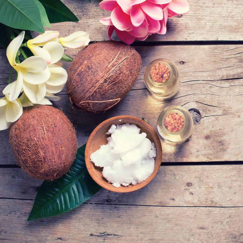 木制背景中的精油浴盐和椰子