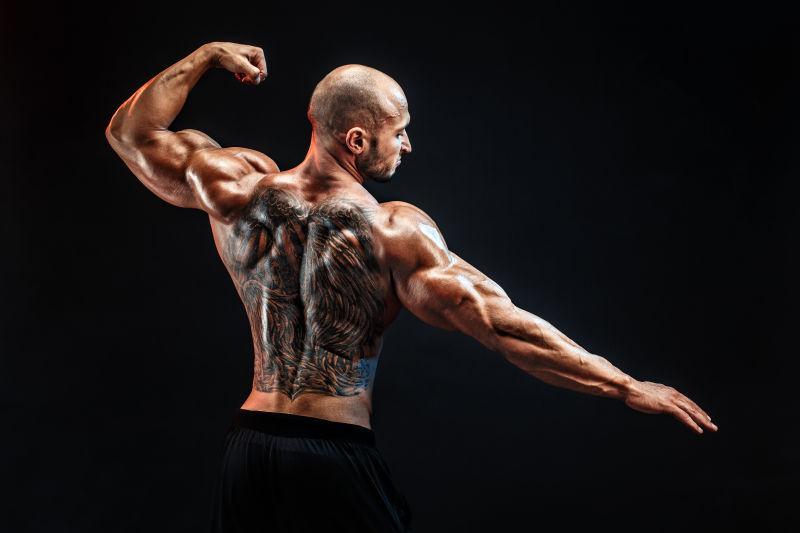 黑色背景下的秃顶纹身的肌肉男人