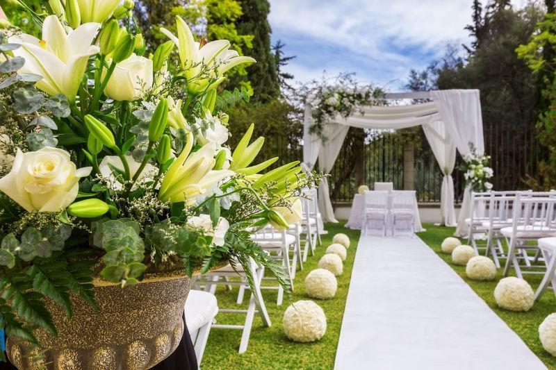 蓝天白云下草地上户外婚礼的过道上的花朵装饰
