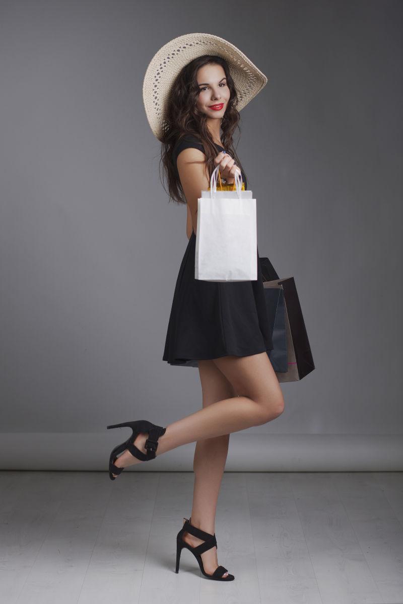 在演播室拍摄的女人拎着购物袋