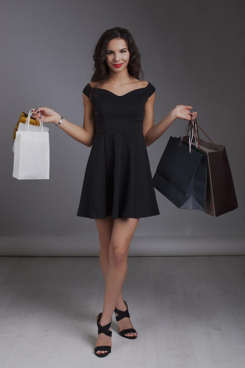 双手拎着购物袋的女人