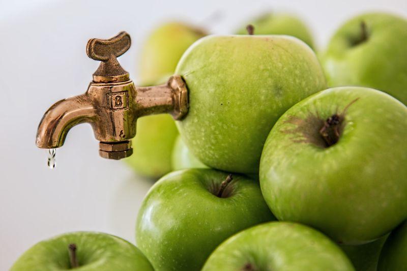 青苹果上的水龙头压榨果汁