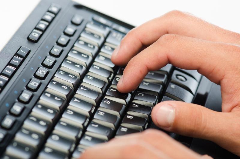 白色背景下在黑色键盘上打字的一双手