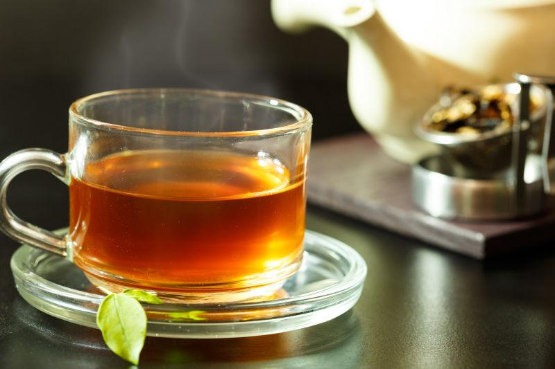 木桌上冒着热气的新鲜的一杯茶