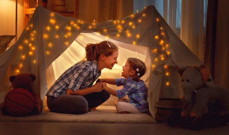 快乐的家庭母亲和女儿在帐篷里玩耍
