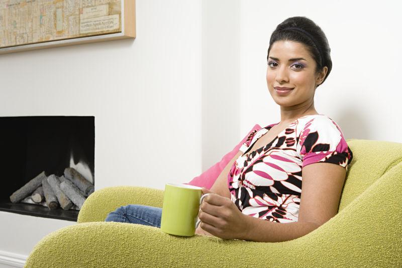 坐在沙发上的美女拿着一个绿色杯子