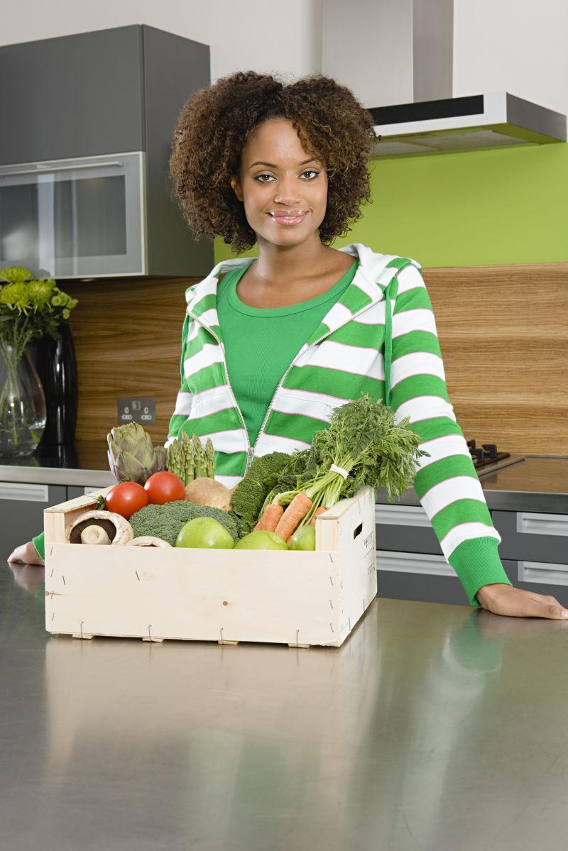 黑人妇女面前的蔬菜箱