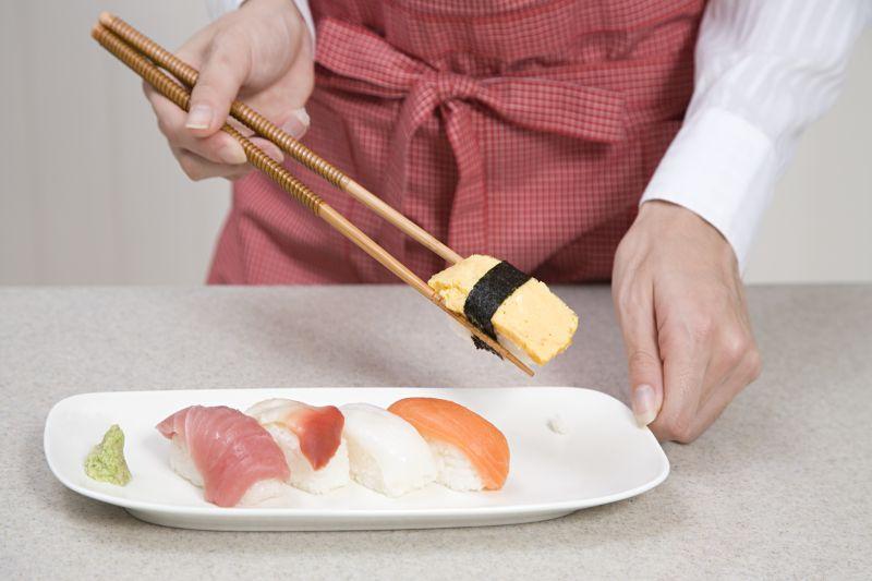 用筷子夹寿司的女人