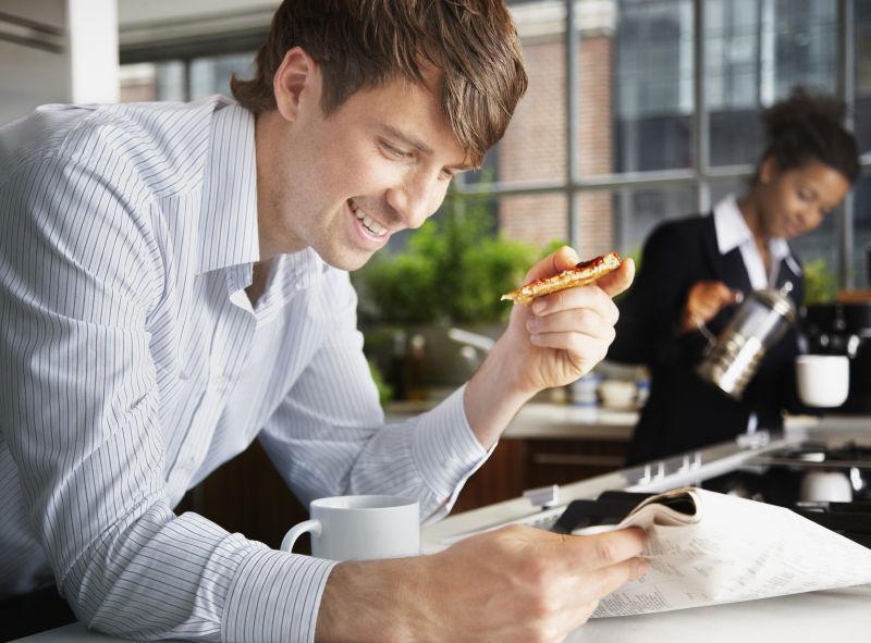 在办公室边看书边吃早点的男人