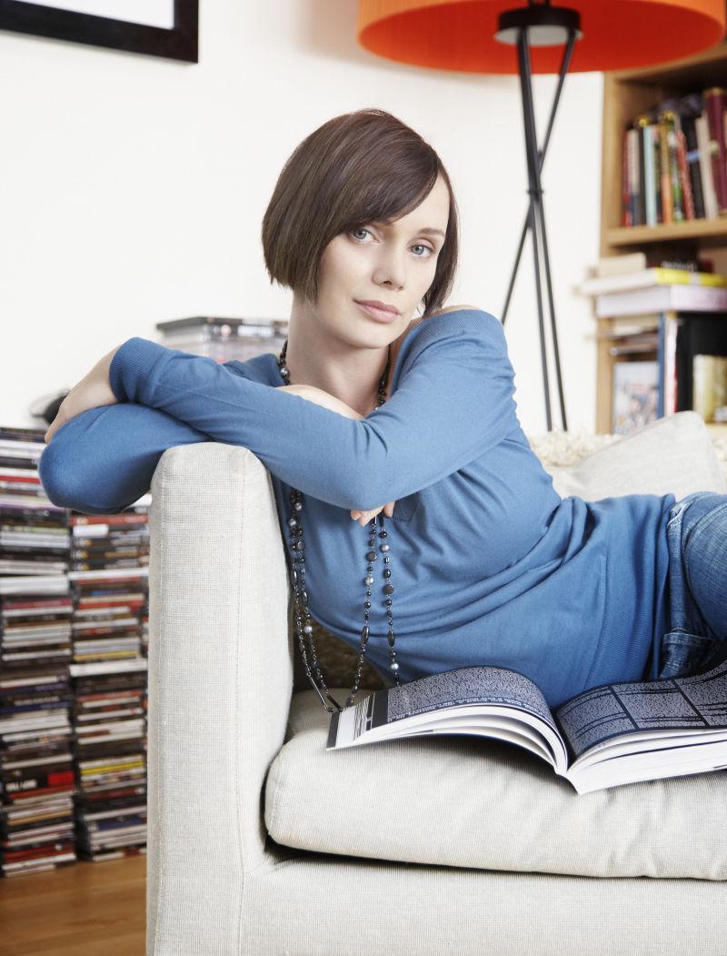 坐在客厅的沙发上看书的年轻女人