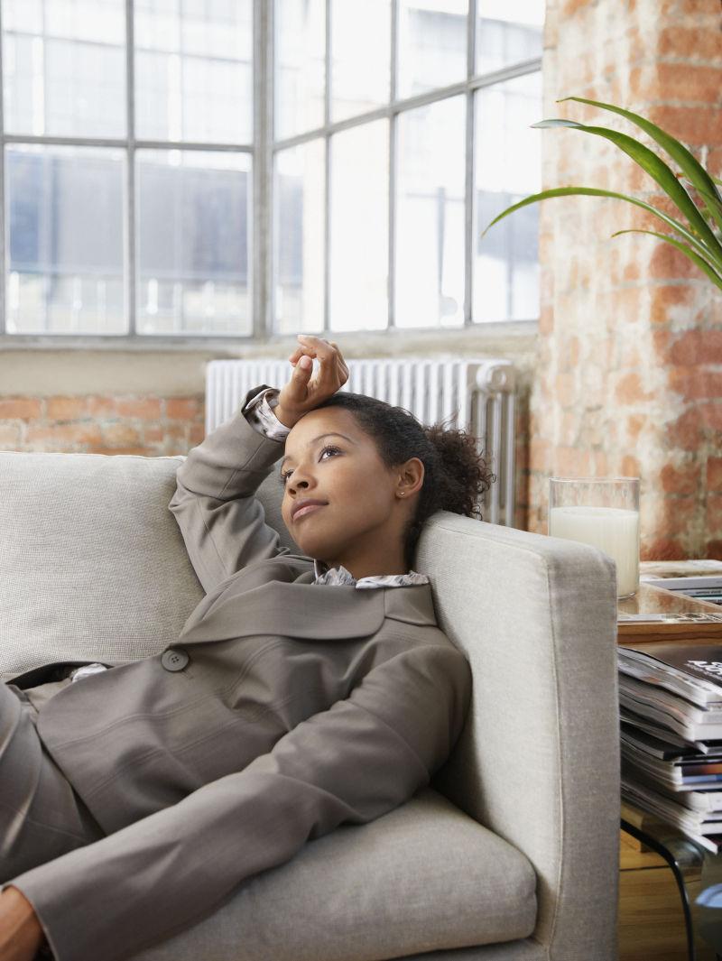 躺在客厅的灰色沙发上思考的穿着工作服的女人
