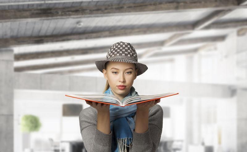 在室内拿着书的年轻美女