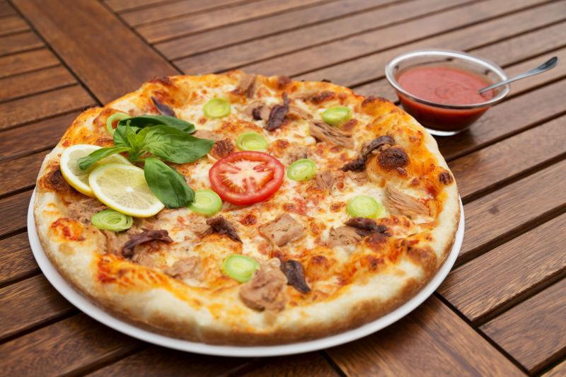 木桌上美味的披萨和番茄酱
