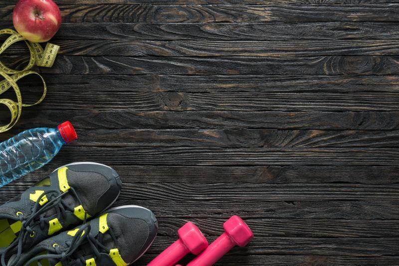粉色的哑铃和球鞋在地板上