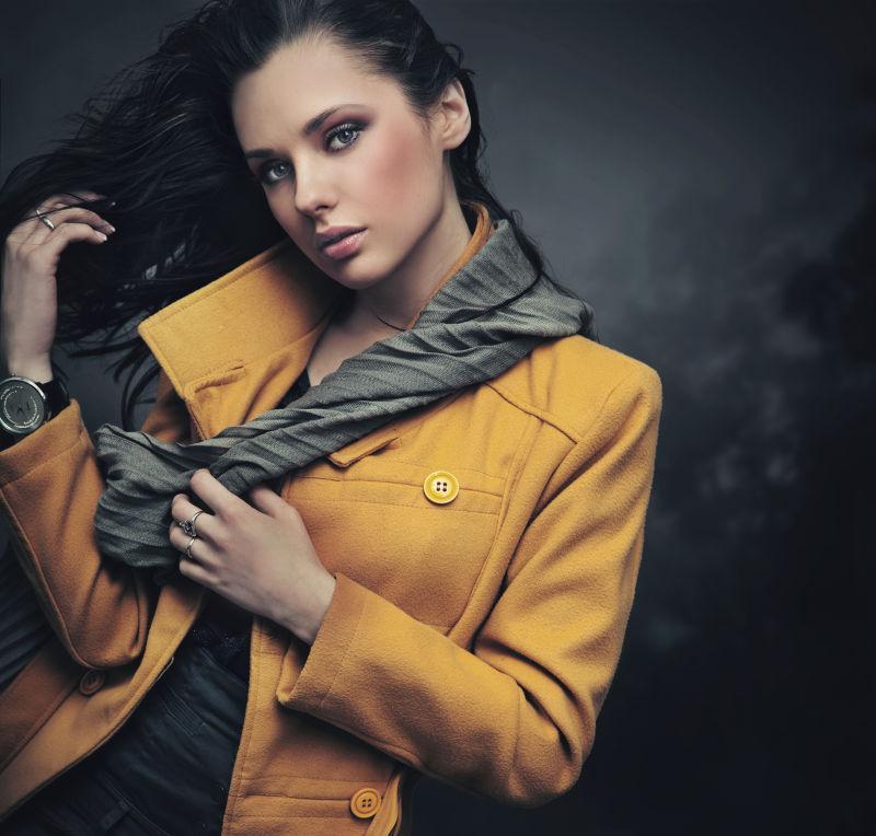 暗色背景上穿着黄色外套的年轻女人