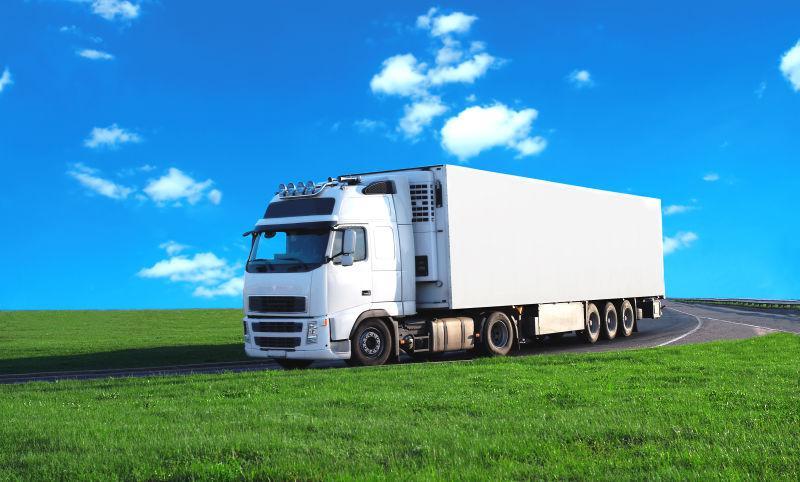 蓝天和草地背景上行驶的白色卡车