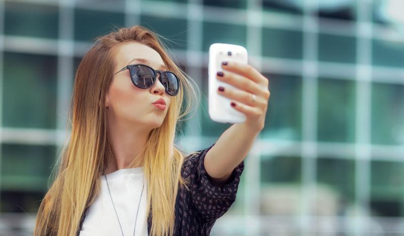 年轻的快乐女孩用他的智能手机自拍