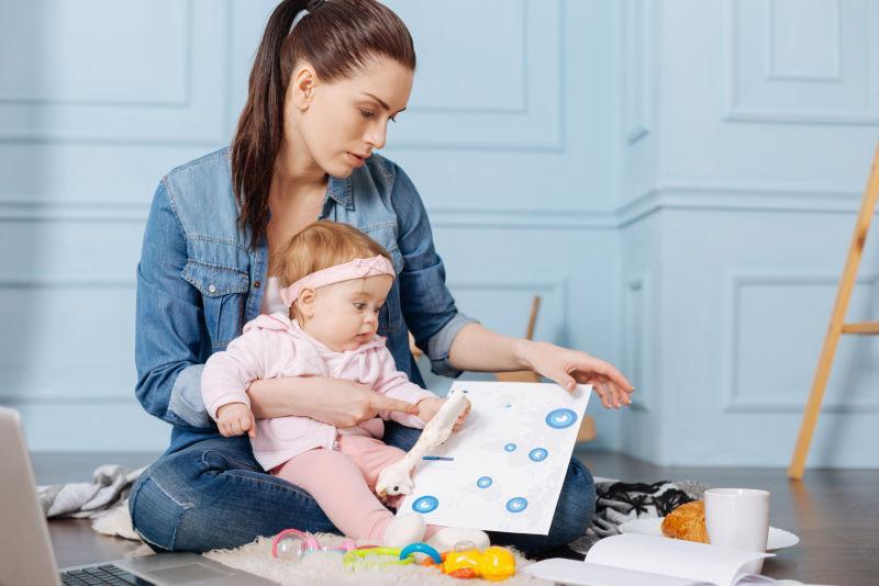 白色室内背景下坐在地板上抱着孩子工作的年轻妈妈